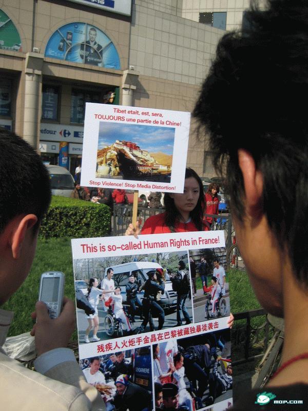 فتاة صينية تحتج في بكين على المعاملة الوحشية لحامل الشعلة