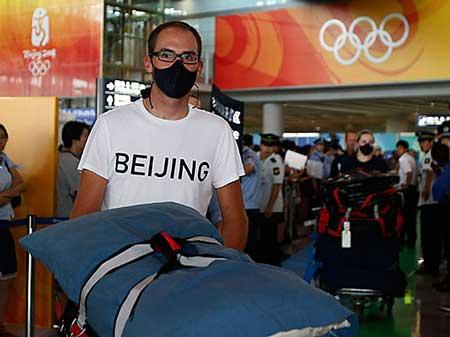 Американските атлетичари со маски на аеродромот во Пекинг