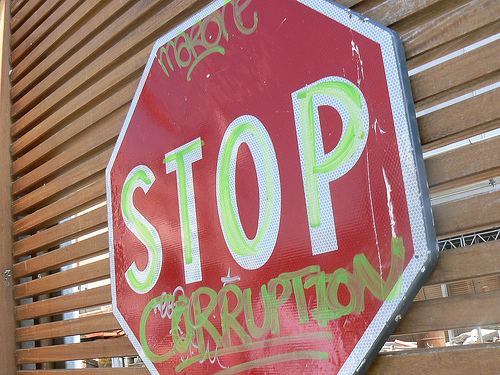 Spray painted Stop Corruption sign