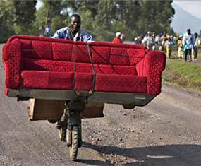 man on a bike carrying a sofa loaded across it