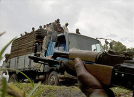 truck loaded with people and machine gun in the foreground