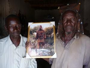 Boukary (à gauche) et son père avec une photo de celui-ci en chasseur. Photo : Toujours Pas Sages, sur Flickr