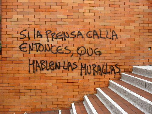 It reads If the press makes silence, then walls should speak. Photo by Juan Arellano. Used with permission. Taken from http://es.zooomr.com/photos/cyberjuan/8272064/