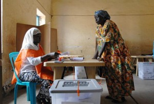 An official from Sudan's National Elections Commission (left) assists a voter at a polling station in Juba, Sudan.