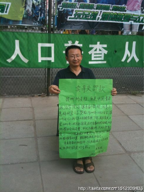 Professor Yang Zhizhu from China Youth University for Political Sciences is holding a placard to sell himself as a slave in order to pay the penalty for violating the one child policy