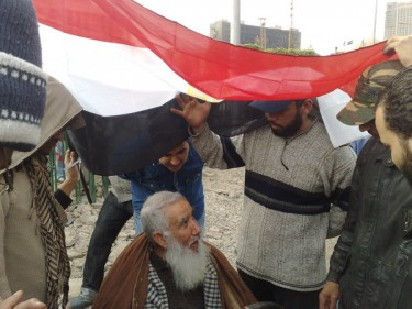 Nadia's father and other protesters take cover from the rain under the Egyptian flag