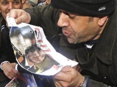 Man spitting on image of Muammar Al Gaddafi. Image posted by @abanidrees.
