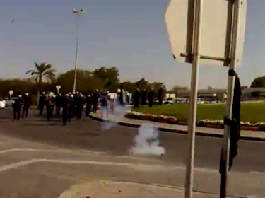 Still from a video showing riot police charging at a peaceful demonstration in Diraz village, Bahrain on 14 February 2011, firing as people flee. Video posted on Youtube by user smodh92.