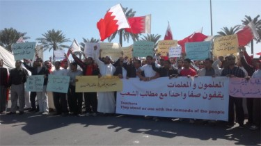 Largest banner: Teachers standing with the people's demands. Taken from the Bahrain Teachers Society website