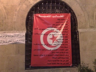 The list of the sit-in protestors' 'Popular Demands' written on the Tunisian flag. Photo by Winston Smith.