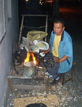 Chinese man using popcorn hammer to pop corn