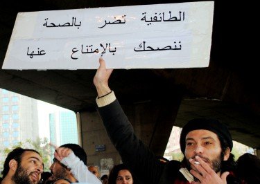 "Smoker holds sign, translation: ""Sectarianism is bad for your health. We suggest avoiding it."" Beirut, Lebanon. Image by Dana Ballout, copyright Demotix (27/02/11)."