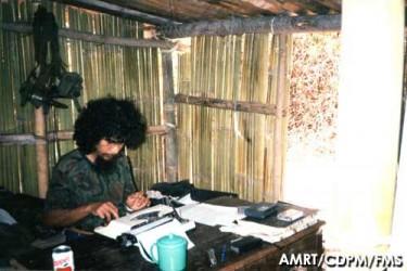 Santana typing in a shelter. By Comissão para os Direitos do Povo Maubere, Arquivo Museu da Resistência Timorense.