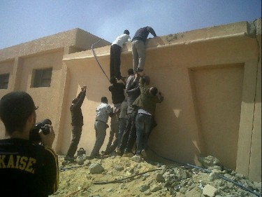 Protesters climbing the State Security building walls to try and save documents from burning