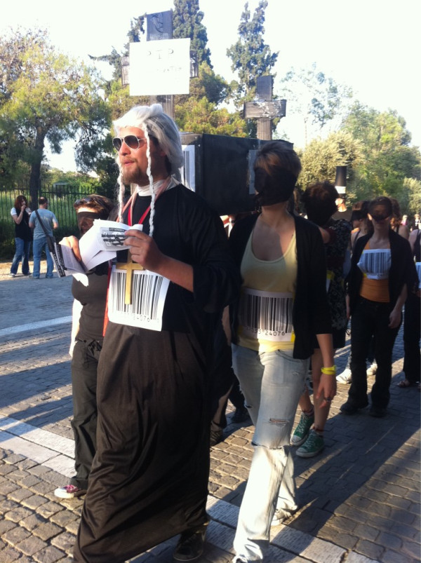 Solidarity protest in Athens: last rites for democracy administered by a corrupt priest. Twitpic photo by Cyberela.