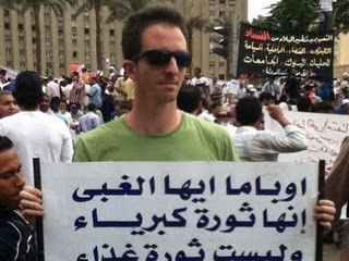 Ilan Grapel in Tahrir Square carrying a poster which calls US President Barack Obama stupid. Source, Ilan Grapel's Facebook account.