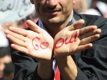 An anti-government protester outside Sana'a University shows the words 'Go Out' to Yemen's President Ali Abdullah Saleh. Image by Flickr user AJTalkEng (CC BY-NC-ND 2.0).