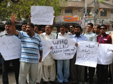 People hold placards demanding an investigation into the killing of Saleem Shahzad. Image by Rajput Yasir, copyright Demotix (01/07/2011).)