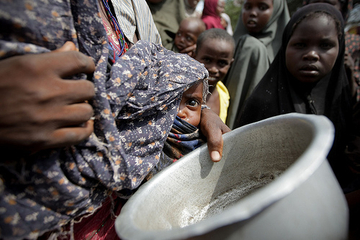 People line up for food at a camp in Mogadishu, Somalia. Image by UN Photo/Stuart Price on Flickr (CC BY-NC-ND 2.0).