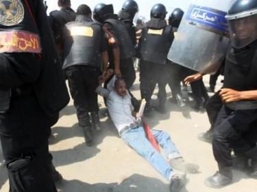 La polizia trascina via il padre di un martire dal processo a Mubarak.