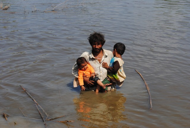 A man with his children under the water moving towards a safe place. Image by Rajput Yasir, copyright Demotix (16/9/2011).