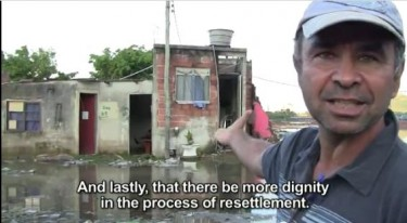 Jorge stands in front of his flooded house where his neighborhood used to stand. Documentary still.