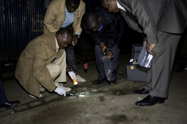 Kenyan police clean up fragments from the explosion. Nairobi, Kenya. Photo by Jonathan Kalan, copyright © Demotix (24th October 2011).