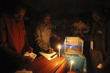 An electoral official checks an election result sheet using a lantern after the Presidential election in Yaounde, Cameroon, Sunday, October 9. 2011 - www.africathroughalens.com