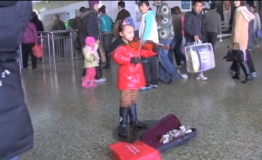 A girl plays the violin at a train station in Beijing