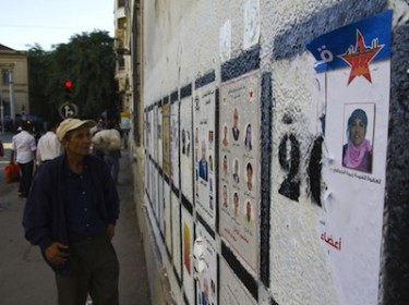 Passerby glances at election posters in central Tunis, Tunisia. Image by Jonathan Mitchell, copyright Demotix (12/10/11).