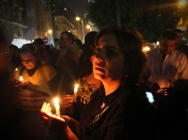 Woman with black clothes holding a candle mourning the Maspero violence. Image by Amr Jamil, copyright Demotix (13/10/11).