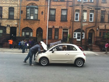 Broken down Fiat being repaired with body double for Jennifer Lopez at the driving wheel. (Photo by Ed Morales)