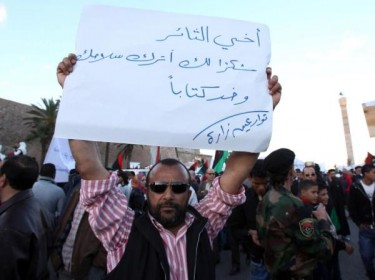 A protester carrying a sign which reads: Dear Revolutionary, Thank your for leaving your weapon behind and carrying a book