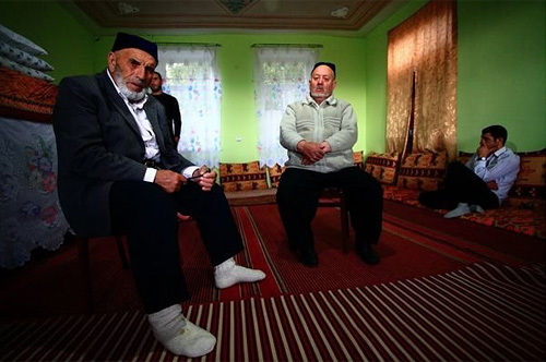 Osman Mekhriev (left) and Islam Niazov, elders of the Abastumani Meskhetian community, take a break from the holiday prayers during the end of Ramazan celebrations © Temo Bardzimashvili