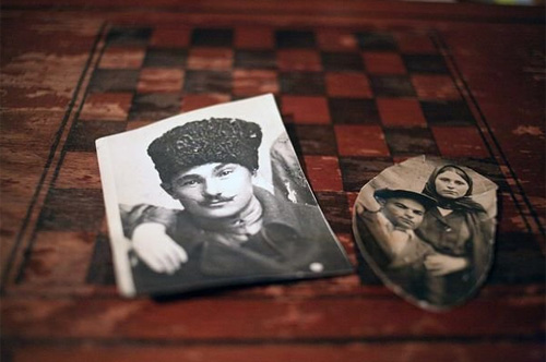 Portraits of Abdullah Gamidov, his wife Khalida, and her father Zia Chumidze lie on the checkerboard in the Gamidov's house in Kant, Kyrgystan. Zia Chumidze was fighting at the frontline when the deportation happened and never made it home. © Temo Bardzimashvili