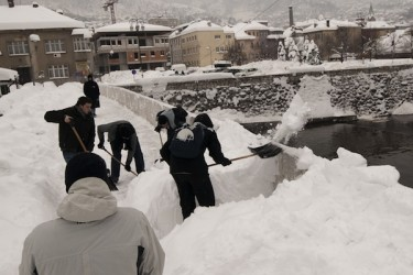 Men shoveling snow from a street in Sarajevo. Record snowfall has paralyzed transportation in the Bosnian capital, where a state of emergency has now been declared. Photo by Sulejman Omerbasic, copyright © Demotix (5/02/12).