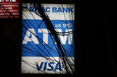 Phone wires entangled around a ATM signboard in Dhaka. Image from Flickr by Joe Athialy. CC BY-NC 2.0