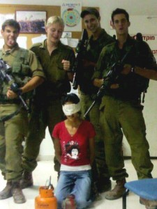 Israeli soldiers posing with a young Palestinian hostage.