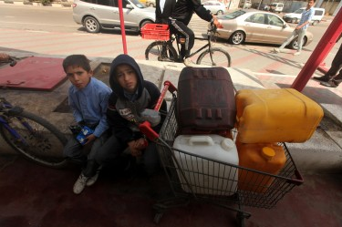 Palestinians wait to fill containers with fuel. Image by Majdi Fathi, copyright Demotix (21/03/2012).