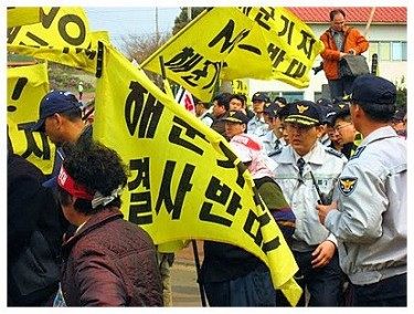 Activists attempt to stop the blasting of coastline in Jeju. By National Campaign to End the Korean War on Facebook.