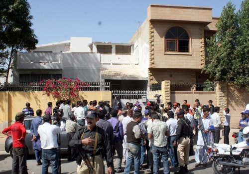 People gather at the house where the dead bodies of five people were found. Image by PPI Images. Copyright Demotix.