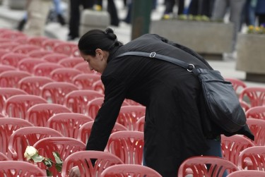 A Bosnian woman, Berina Hodzic, lays a flower on one of the red chairs that were installed along Sarajevo's main street to mark the 20th anniversary of the start of the Bosnian War. Photo by SULEJMAN OMERBASIC, copyright © Demotix (04/06/12).