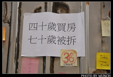 A poster outside Wang's houses. It says 'my house was bought when I was 40, and it was torn down when I was 70.' Photo by Flickr User munch999 (CC BY-NC-SA 2.0).
