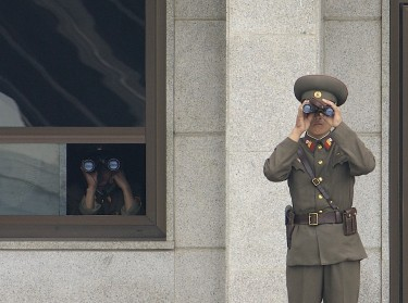 North Korean soldiers look south while on duty in the Joint Security Area, Korean Demilitarized Zone. Image is in the public domain, via Wikipedia.