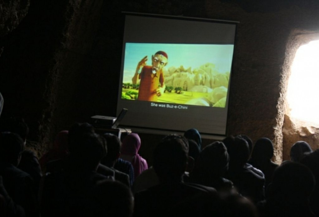 Children from Bamyan watch 'Buz-e-Chini' on a screen mounted in a cave. Photo by Tahira Bakhshi (The Republic of Science), used with permission.