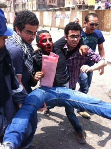Wounded and bloodied being carried away from Abbassiya. Image by Twitter user @sharifkouddous.