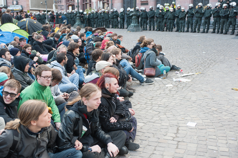 Protesters sit down and lock arms in opposition to police presence. Photo by Patrick Gerhard Soesser, copyright Demotix (May 17, 2012).