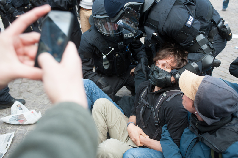 A protester is detained by police. Photo by Patrick Gerhard Stoesser, copyright Demotix (May 17, 2012).