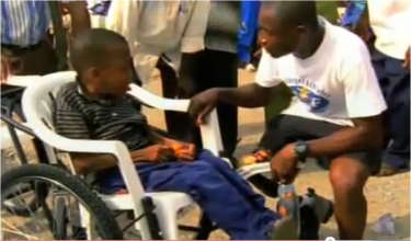 Yeboah discussing overcoming disabilities with a child in a wheelchair. Screenshot from the documentary Emmanuel's Gift