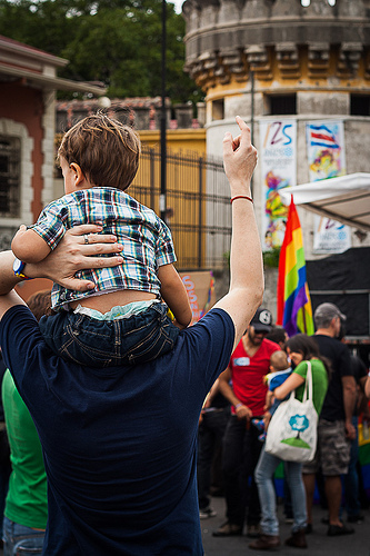 Man carries a baby on his shoulders during the Invisibles March in Costa Rica